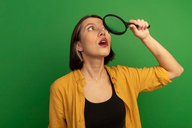 Verrast vrij blanke vrouw houdt en kijkt naar vergrootglas op groen
