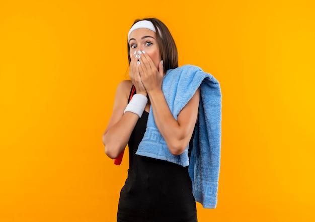 Verrast vrij sportief meisje hoofdband en polsbandje met handdoek dragen en touwtjespringen op schouders handen op mond geïsoleerd op oranje ruimte
