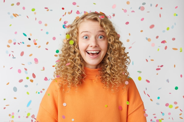 Verrast vrolijk geïnspireerde blondine met wijd open blauwe ogen vrolijk lachend voelt zich blij tevreden gekleed in een oranje oversized trui staat onder de vallende confetti