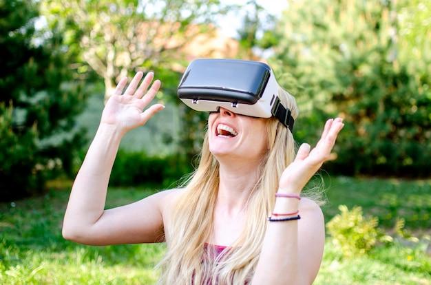 Verrast vrolijke vrouw met behulp van 3d vr-virtual reality headset. blonde opgewonden vrouw gebaren tijdens het gebruik van digitaal entertainment buiten in de groene natuur. gelukkige jonge vrouw op zoek naar 3d digitale film