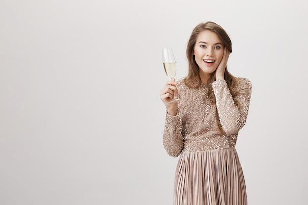Verrast vrouw in avondjurk met glas champagne