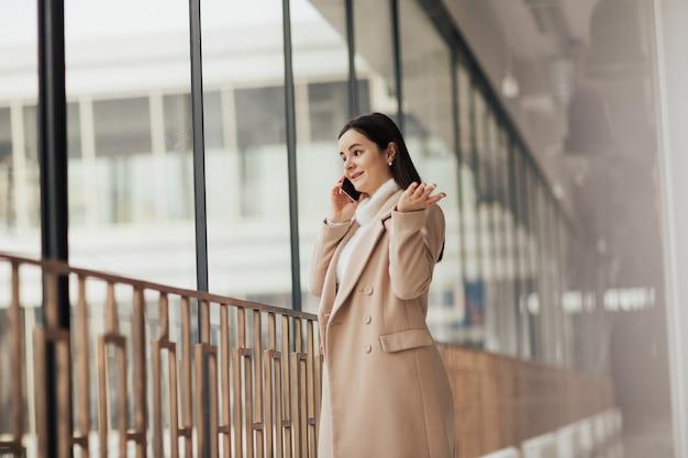 Verrast vrouw in beige jas praten over smartphone, permanent in de buurt van panoramisch raam in de stad.