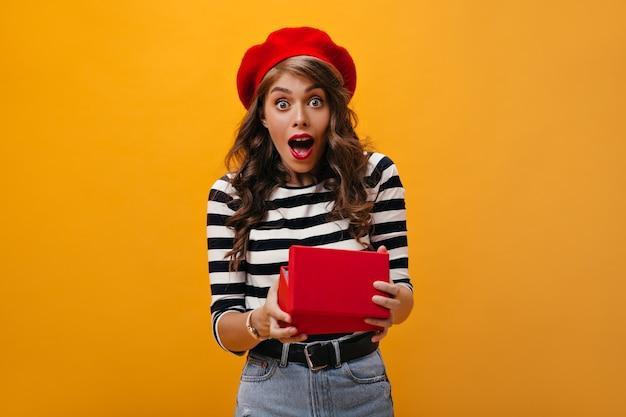 Verrast vrouw in rode baret geschenkdoos openen op oranje achtergrond. mooi meisje met golvend kapsel in lichte hoed en moderne kleding verheugt zich.