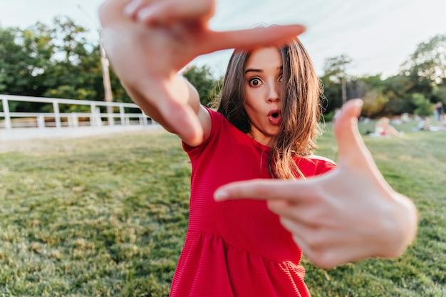 Verrast vrouw in rode kleding buiten poseren en grappige gezichten maken. foto van emotionele bruinharige meisje koelen in de lentedag.