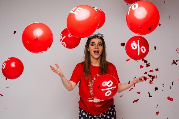 Verrast vrouw in t-shirt en comfortabele broek gooit veel luchtballonnen over