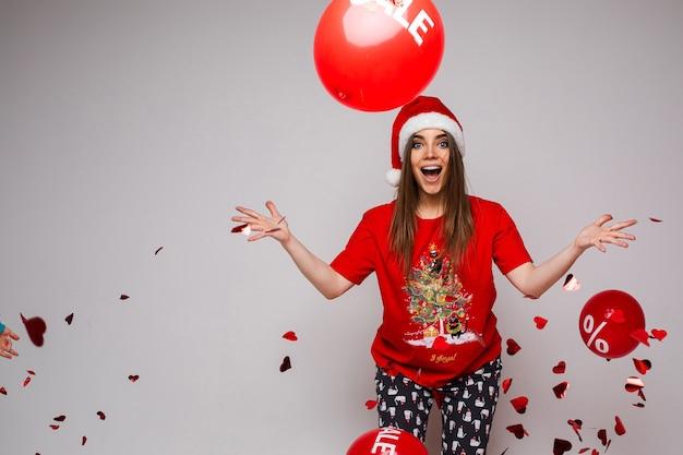 Verrast vrouw in t-shirt en comfortabele broek met rode en witte kerstmuts op haar hoofd
