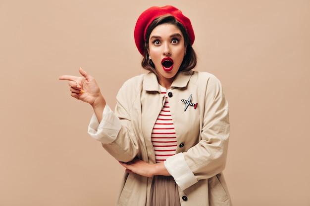 Verrast vrouw in trenchcoat wijst naar plaats voor tekst op beige achtergrond. modern meisje in lange jas en hoed die en camera stellen onderzoeken.