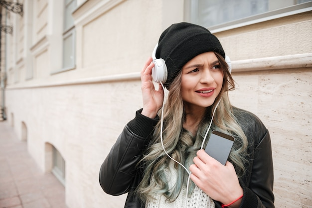 Verrast vrouw in warme kleding luisteren muziek op straat