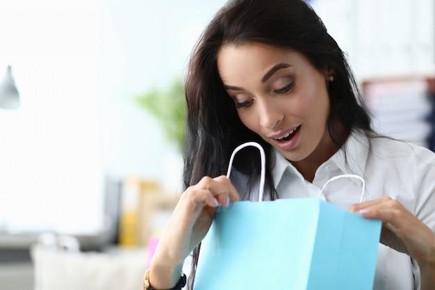 Verrast vrouw loock in blauwe papieren zak tegen