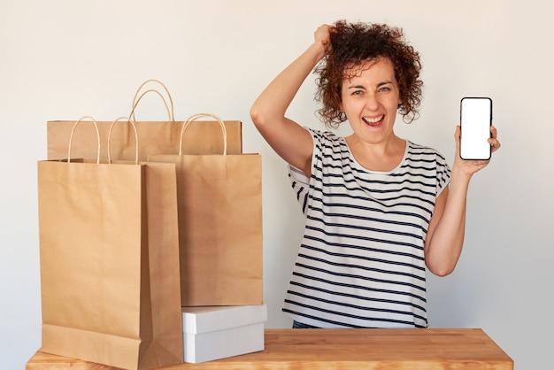 Verrast vrouw met een smartphone naast boodschappentassen