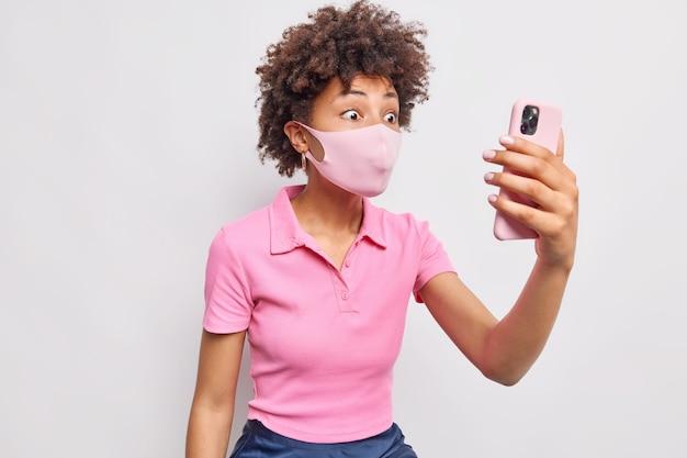 Verrast vrouw met krullend haar draagt steriel wegwerpmasker in zelfisolatie besmet met coronavirus belt op afstand via smartphone gekleed in casual roze t-shirt geïsoleerd over witte muur