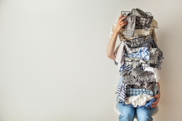 Verrast vrouw met metalen wasmand met rommelige kleren op witte achtergrond.
