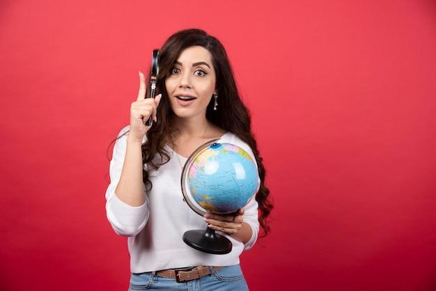 Verrast vrouw poseren met globe en vergrootglas. hoge kwaliteit foto