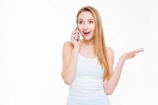 Verrast vrouw praten aan de telefoon geïsoleerd op een witte achtergrond