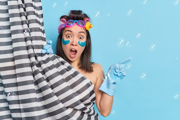 Verrast vrouwelijk model houdt mond open reageert op iets schokkends wijst weg over blauwe achtergrond met bubbels