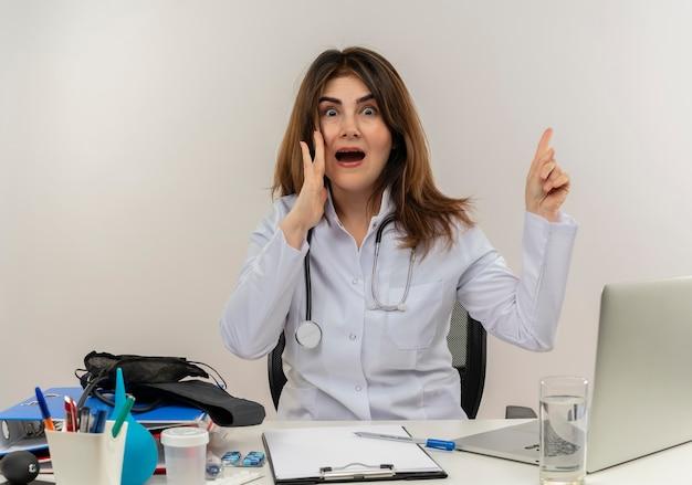 Verrast vrouwelijke arts van middelbare leeftijd die het dragen van medische mantel met een stethoscoop zittend aan een bureau werkt op laptop met medische hulpmiddelen hand op de wang plaatsen wijst naar de witte muur