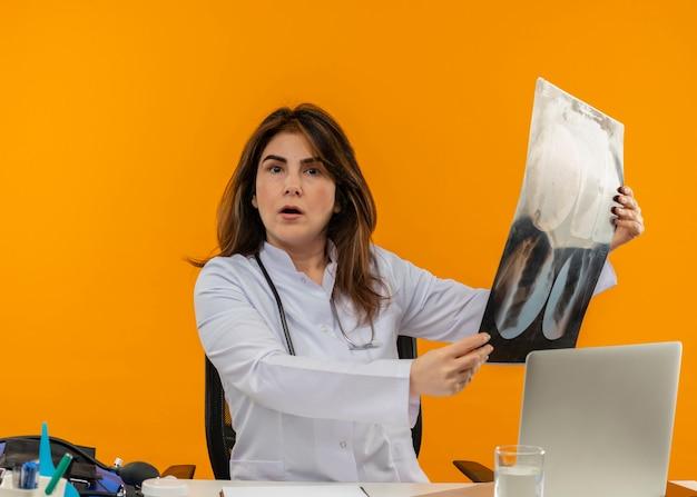 Verrast vrouwelijke arts van middelbare leeftijd dragen medische gewaad met stethoscoop zit aan bureau werken op laptop met medische hulpmiddelen x-ray houden op geïsoleerde oranje achtergrond met kopie ruimte