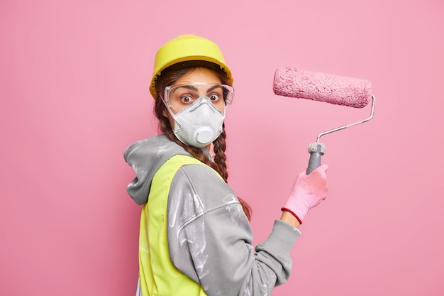 Verrast vrouwelijke schilder verhuist in nieuwe woning druk bezig met repareren houdt verfroller vast