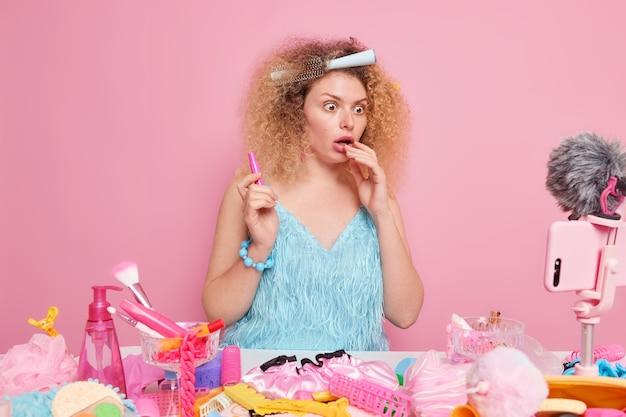 Verrast vrouwelijke schoonheidsblogger geeft make-up videoles staart geschokt naar smartphone webcam houdt cosmetische procut heeft krullend haar met vastzittende kam poses tegen roze achtergrond neemt vlog op