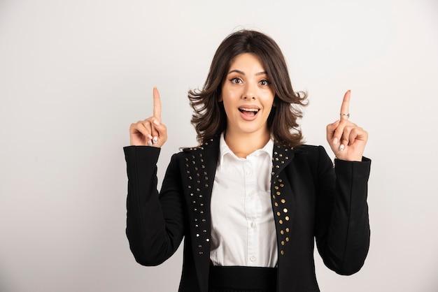 Verrast vrouwelijke werknemer wijzend op bovenkant