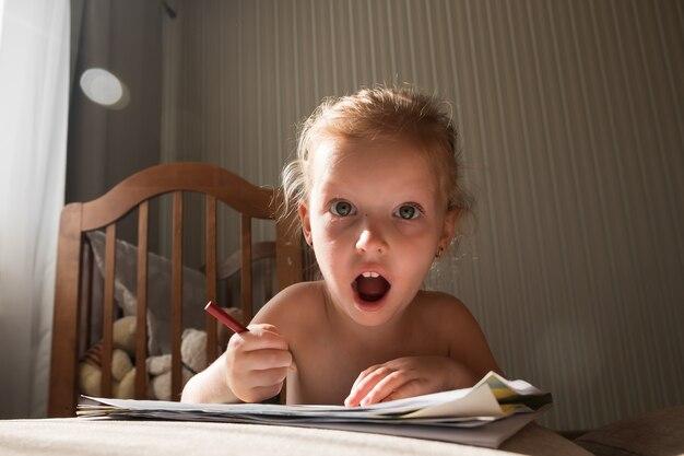 Verrast weinig blonde meisjestekening met potloden op bank thuis. thuis in quarantaine plaatsen