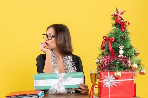 Verrast zakelijke dame in pak met bril in diepe gedachten wijzend haar geschenk en zittend aan een tafel met een kerstboom erop in het kantoor