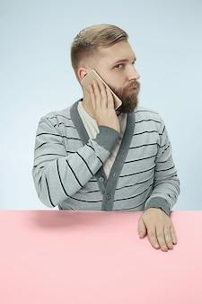 Verrast zakenman praten over de telefoon aan de tafel zitten.