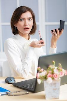 Verrast zakenvrouw doet make-up op kantoor