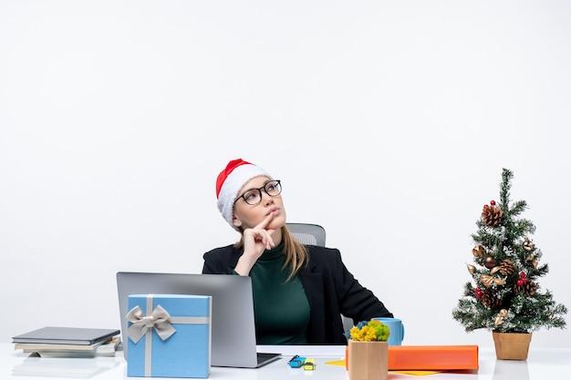 Verrast zakenvrouw met kerstman hoed zittend aan een tafel met een kerstboom en een cadeau erop en wijst naar boven aan de linkerkant op witte achtergrond