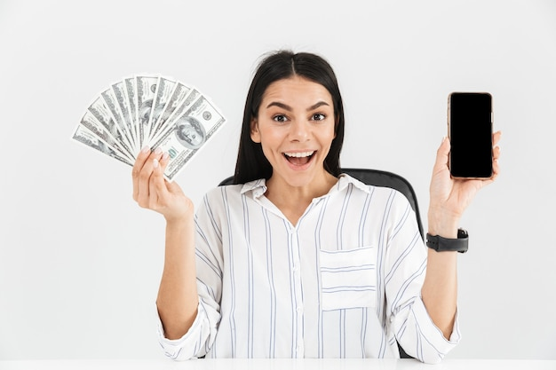 Verrast zakenvrouw smartphone en ventilator met dollar geld bankbiljetten zittend in fauteuil in kantoor geïsoleerd over witte muur te houden