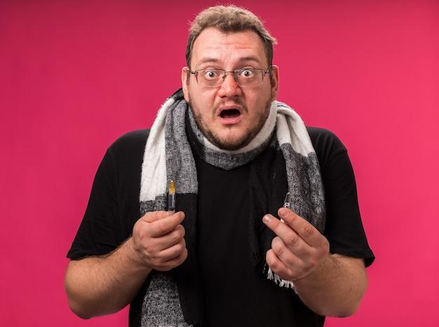Verrast ziek mannetje van middelbare leeftijd met een sjaal die een spuit met een ampul vasthoudt