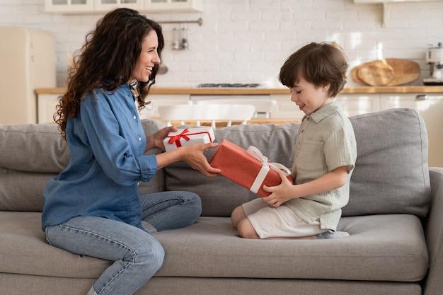 Verrast zoon en moeder cadeautjes uitpakken jong gezin van twee mensen wisselen opgewonden blije cadeaus uit