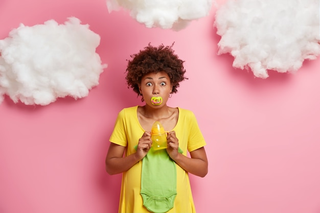 Verrast zwangere toekomstige moeder houdt tepel in mond poses met babykleertjes en benodigdheden maakt zich klaar voor kraamkliniek poses binnenshuis