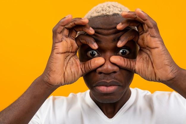 Verrast zwarte afrikaanse jonge man bedekt zijn gezicht met zijn handen en puilt zijn ogen op geel