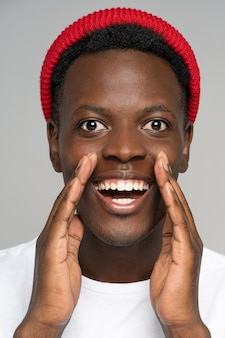 Verrast zwarte man hand in hand in de buurt van mond