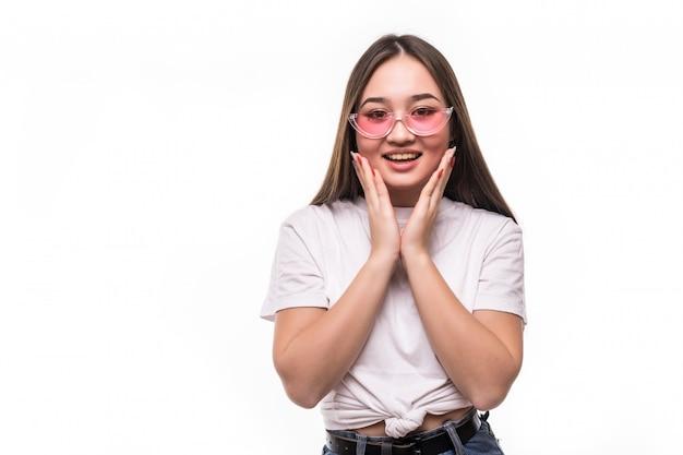Verraste aziatische vrouw in zonnebril die op witte muur wordt geïsoleerd