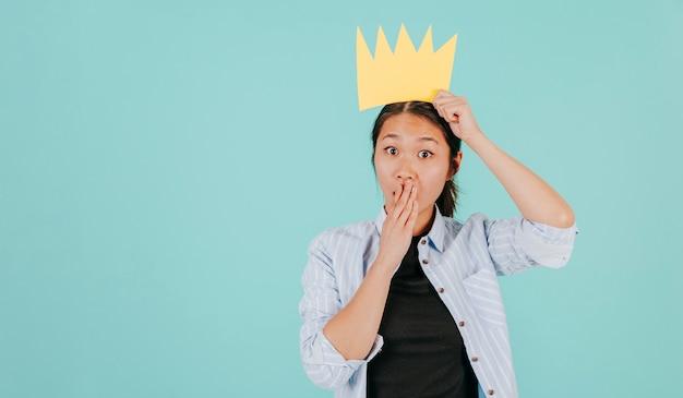 Verraste aziatische vrouw met papieren kroon