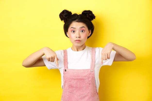 Verraste aziatische vrouw met schoonheidsmake-up, wijzende vingers naar beneden en kijkt opgewonden, toont interessant geel nieuws.