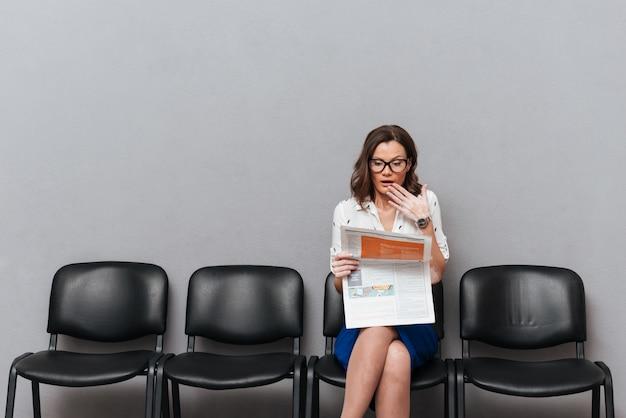 Verraste bedrijfsvrouw die in oogglazen op stoelen zitten