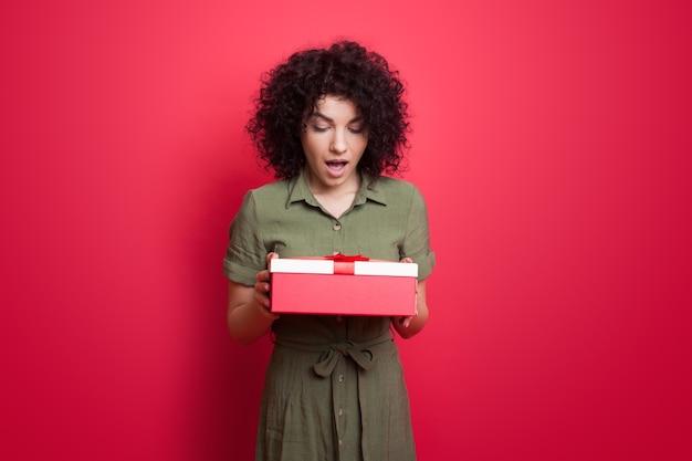 Verraste blanke vrouw met krullend haar die jurk draagt en een geschenk houdt dat zich voordeed op een rode studiomuur