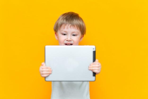Verraste blonde drie jaar oude jongens met zijn open mond verrast, houdend in zijn handen een tabletpc en bekijkend de camera