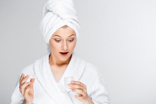 Verraste blonde vrouw in badkamers die room toont
