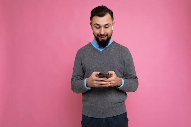 Verraste coole knappe brunet ongeschoren jonge man met baard met grijze trui