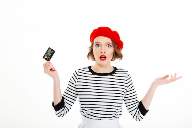 Verraste dame die in rode baret camera met uitgestrekte geïsoleerde handen kijkt