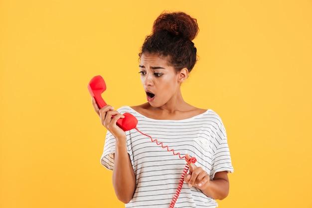 Verraste dame die rode zaktelefoon bekijkt die over geel wordt geïsoleerd