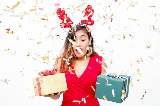 Verraste emotionele vrouw die gift kiest onder confetti