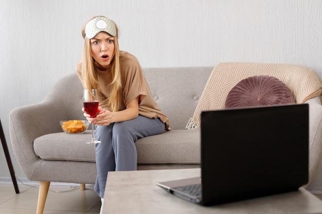 Verraste emotionele vrouw met een glas wijn op de laag die in laptop staart