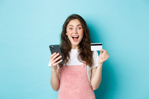 Verraste en gelukkige jonge vrouw die plastic creditcard en smartphone toont, verbaasd naar de camera kijkt, online winkelt met lentekortingen, blauwe achtergrond.