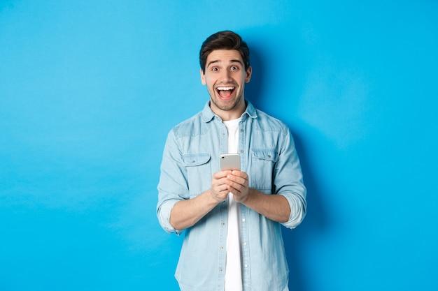 Verraste en gelukkige man die iets online wint, smartphone vasthoudt en zich verheugt, staande tegen een blauwe achtergrond