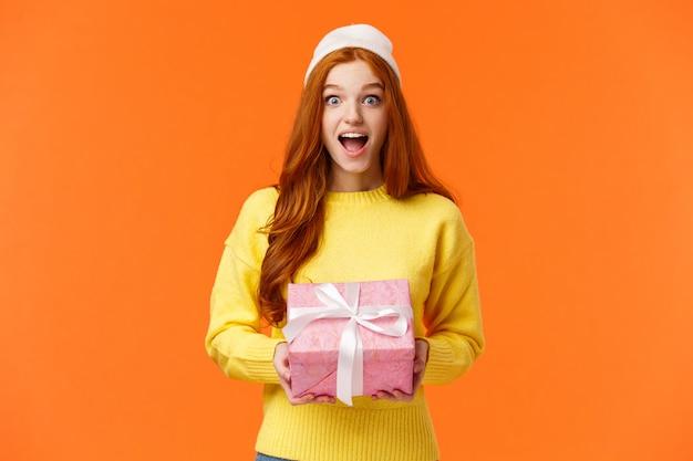 Verraste en opgewekte gelukkige vrouw die giften op kerstavond, nieuwe jaarviering uitpakken